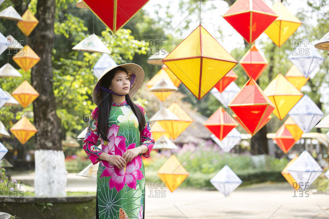 Vietnam, Thua Thien Hue, Hue - March 2, 2018: A young Vietnamese in traditional hat is surrounded by lanterns.