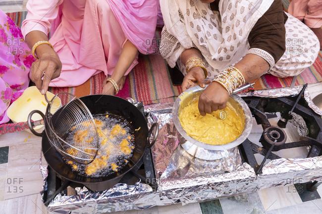 Women's hands make pakoras (Indian chickpea-battered fritters).