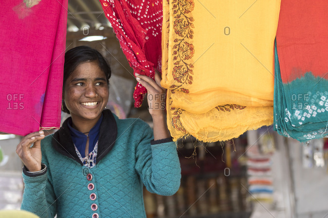 India, Rajasthan, Shaitrawa - January 28, 2019: A young woman peek out between colorful Indian clothes and smiles.