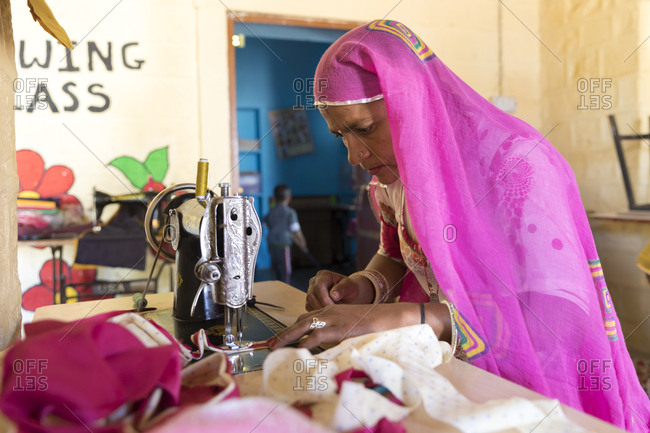 India, Rajasthan, Shaitrawa - January 28, 2019: An Indian woman sews with an old Singer sewing machine.