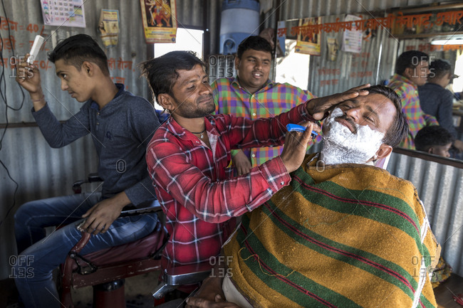 India, Rajasthan, Shaitrawa - January 28, 2019: A man shaves another man in an Indian barber shop.