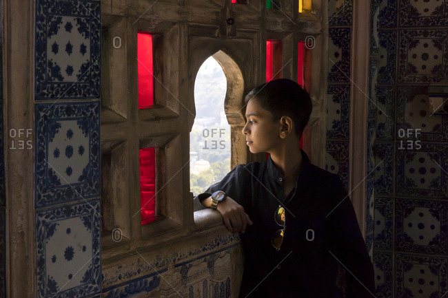 India, Rajasthan, Udaipur - January 28, 2019: A young boy looks out of a window at City Palace in Udaipur, India.