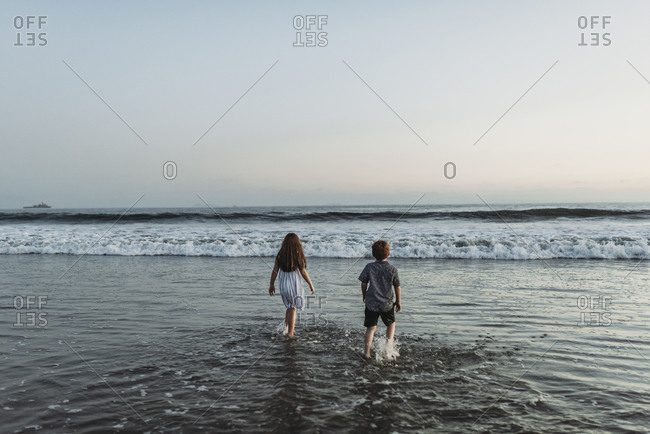 Siblings walking into the ocean staring at the horizon at sunset