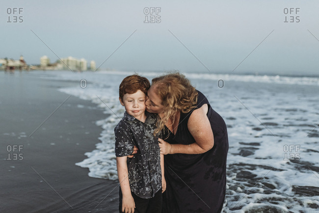 Son making funny face while mother kisses him at dusk at the beach