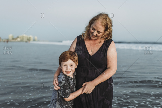 Portrait of son smiling with mother at dusk in the ocean at beach