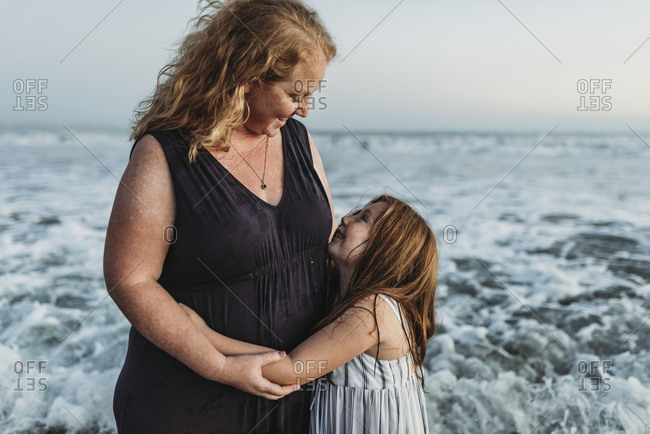 Side view of happy young daughter hugging mother in ocean at dusk
