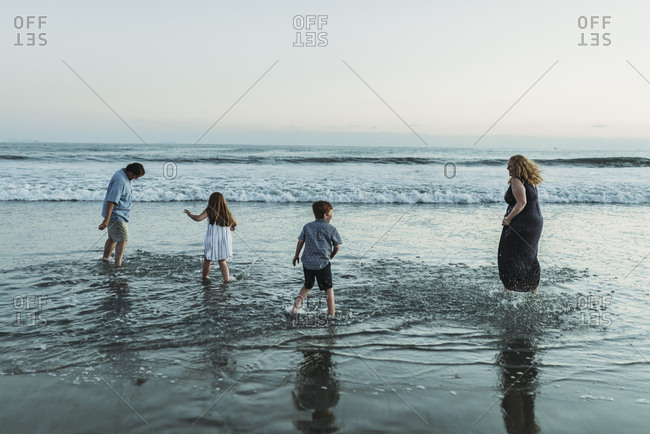 Family of four playing and splashing each other in ocean at dusk