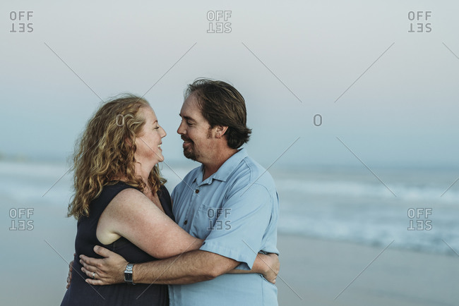 Side view of husband and wife looking at each other at the beach