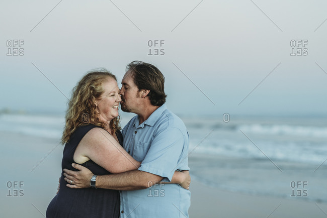 Side view of husband and wife kissing each other at the beach