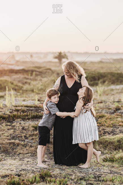 Portrait of redhead mother hugging children at sunset at beach