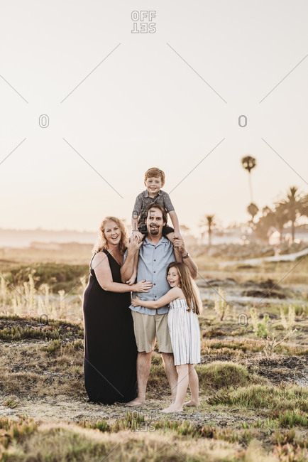 Portrait of happy smiling family of four hugging on beach at sunset