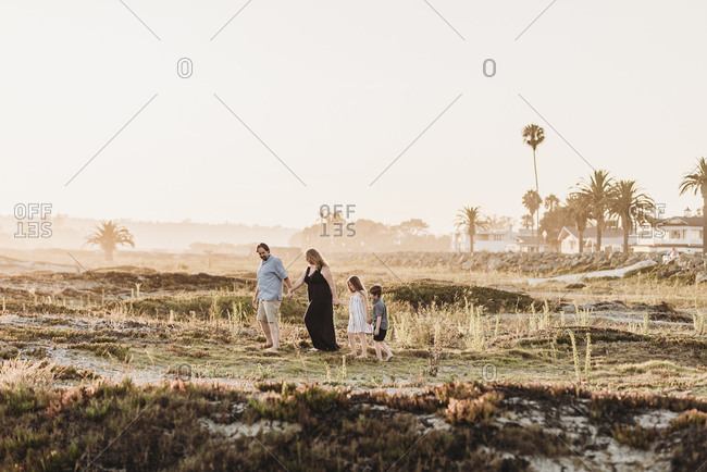 Side view of happy family of four walking and holding hands at beach