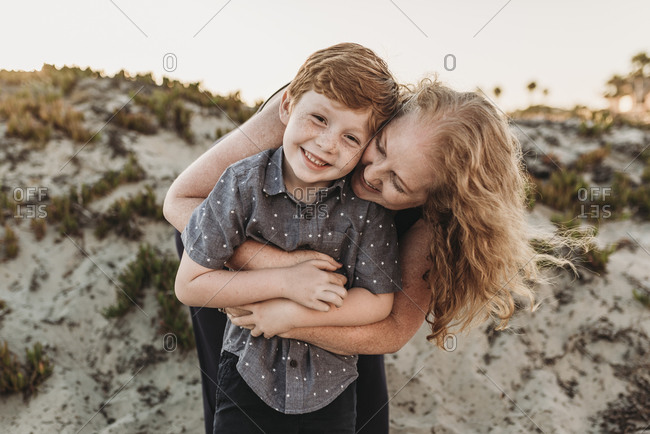 Front view of mother hugging redheaded kindergarten age son at sunset