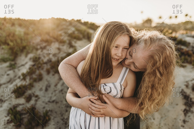 Front view of mother hugging young daughter at beach during sunset