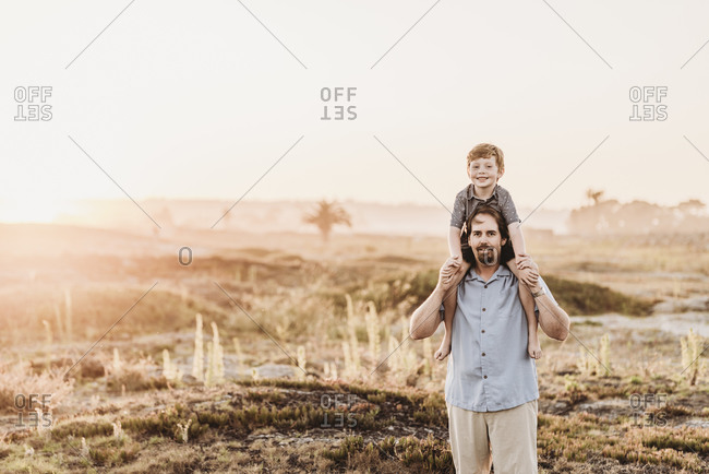 Father holding son up on shoulders while smiling at camera at beach