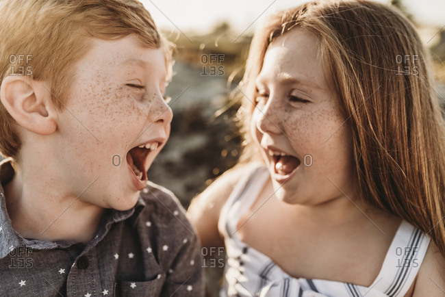 Side view of young freckled redhead siblings laughing at each other