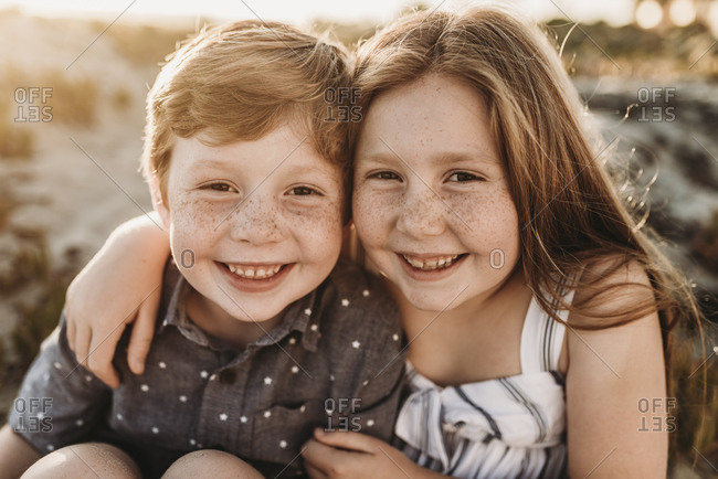 Portrait of young redheaded freckled siblings smiling during sunset