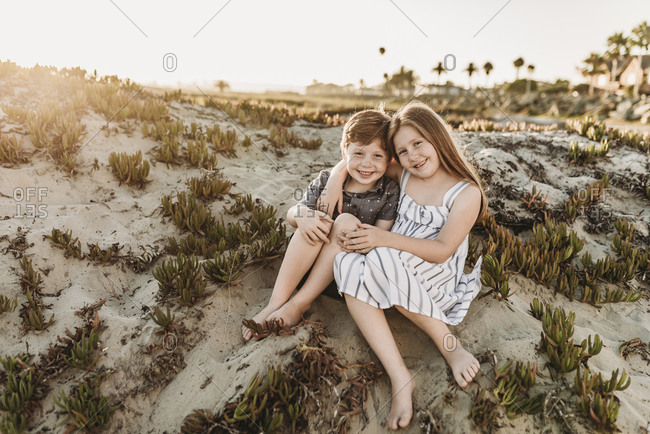 Front view of young redheaded freckled siblings sitting at beach