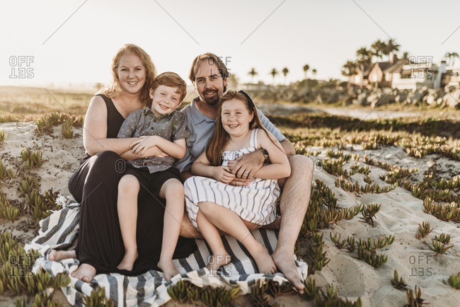 Portrait of family of four sitting on blanket at beach during sunset