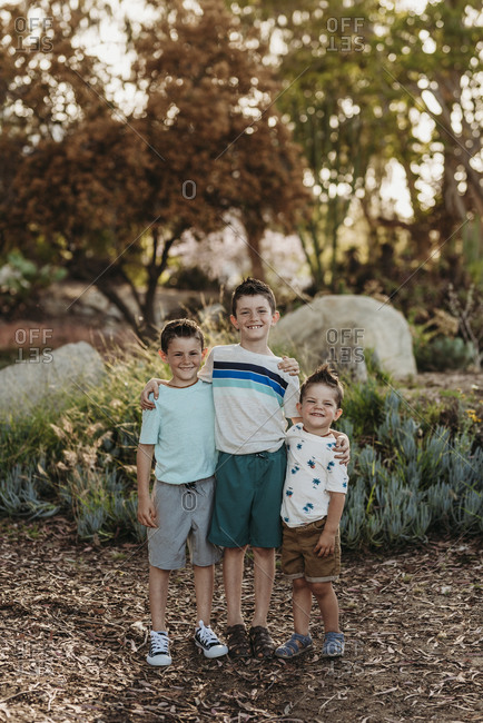 Portrait of three brothers smiling at camera in cactus garden