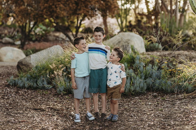 Portrait of three brothers smiling at each other in cactus garden