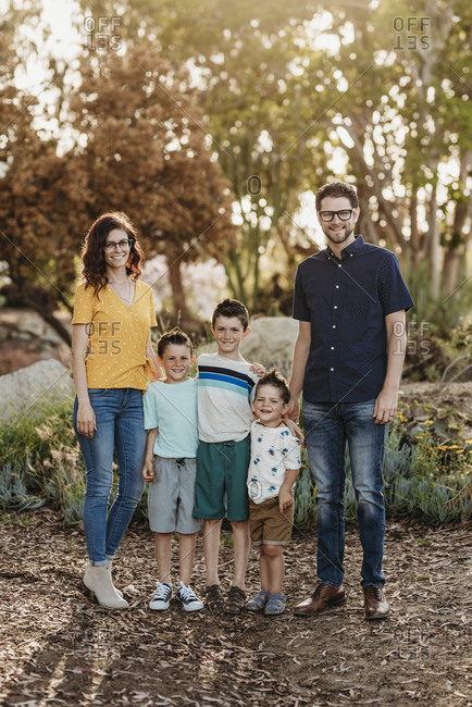 Portrait of family smiling at camera in sunny cactus garden