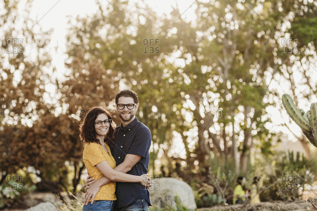 Portrait of husband and wife smiling at camera in sunny cactus garden