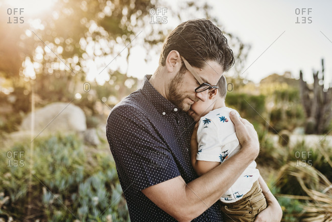 Portrait of father embracing young toddler son with sun behind them