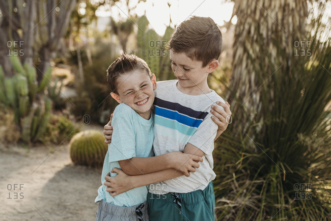 Cheerful brothers embracing and smiling in sunny cactus garden