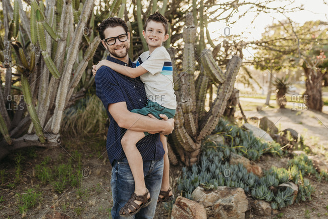 Portrait of father holding older son and smiling at the camera