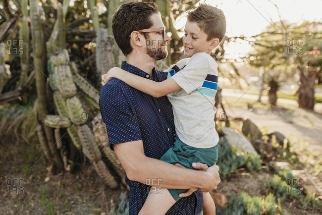 Portrait of father holding older son and smiling at each other
