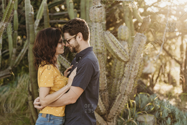 Husband and wife hugging each other in sunny cactus garden