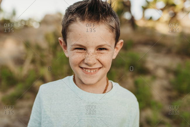Close up portrait of cute young boy with freckles smiling