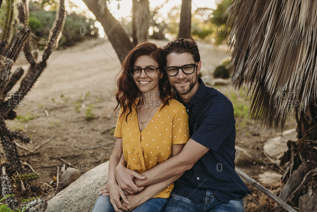 Mid adult married couple sitting on rock smiling as they hug close