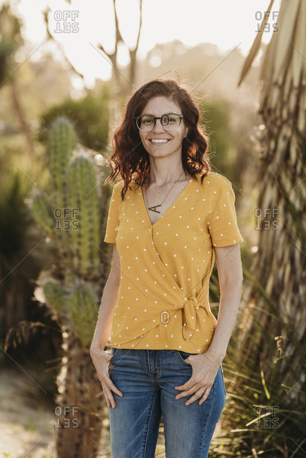 Headshot of young mother wearing glasses in backlight cactus garden