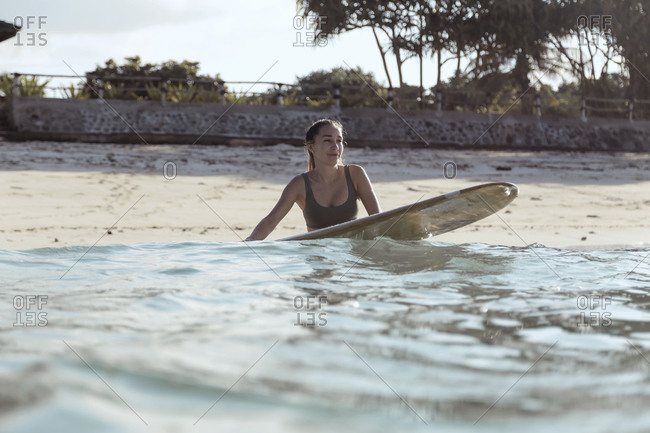 Young woman with surfboard on the beach