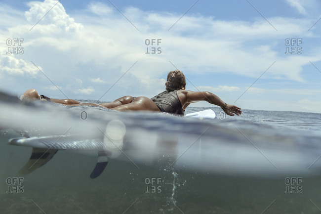 Woman lying on surfboard on the sea