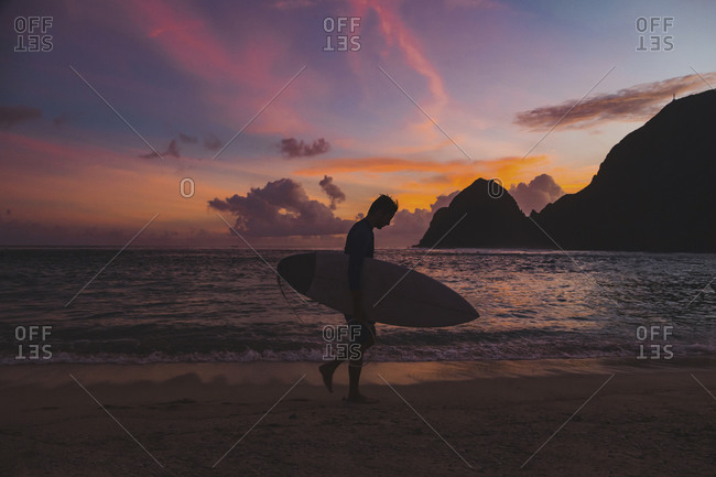 Surfer at the beach at sunset time
