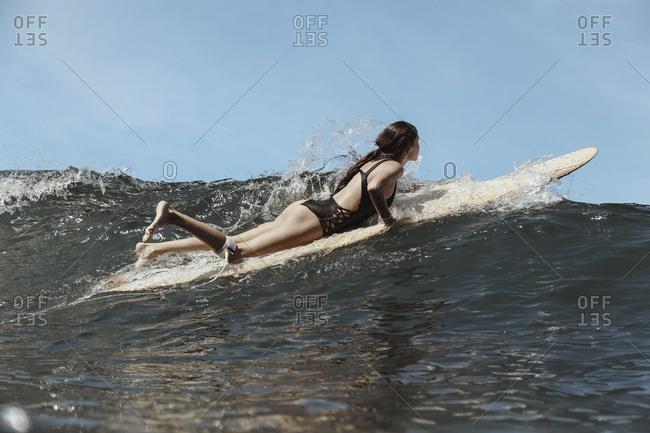 Girl surfing in ocean