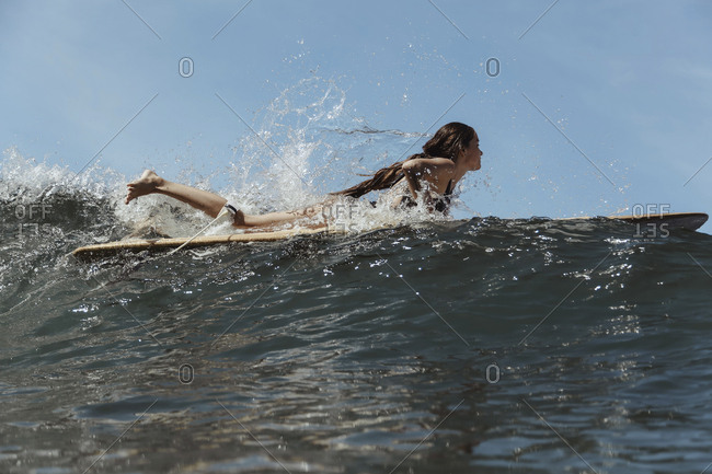 Girl surfing in ocean