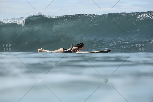 Female surfer in the ocean waiting for a wave