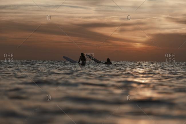 Surfers in ocean at sunset
