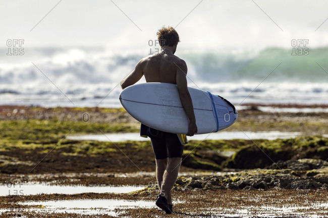 Man with surfboard walking on the beach