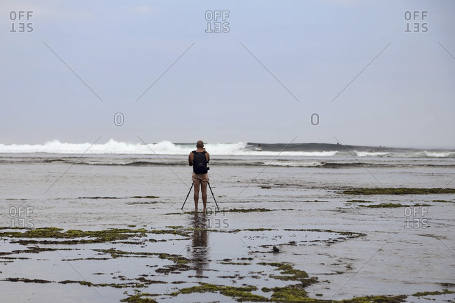 Photographer with tripod making a surfer's shooting