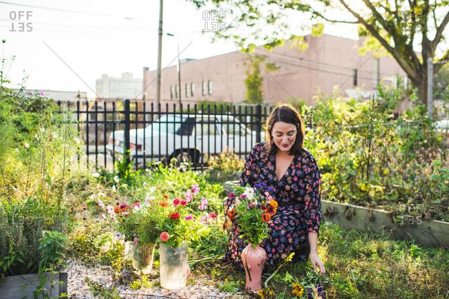 happy woman picking flowers in urban garden