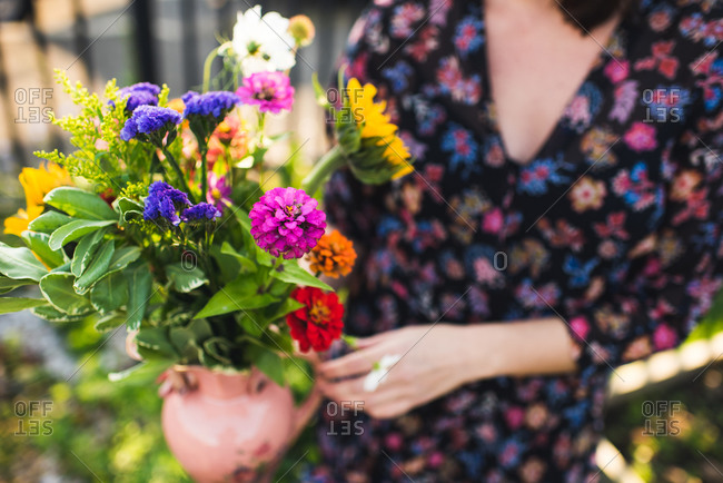 gorgeous summer flowers held by woman in garden