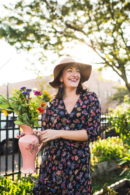 happy woman holding fresh flowers in urban setting