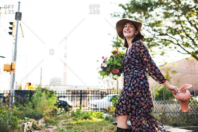 happy woman walking through urban garden with flowers