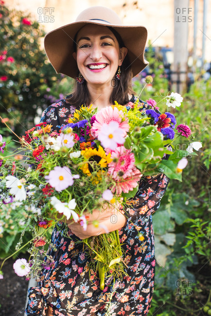 happy smiling woman in garden with flowers