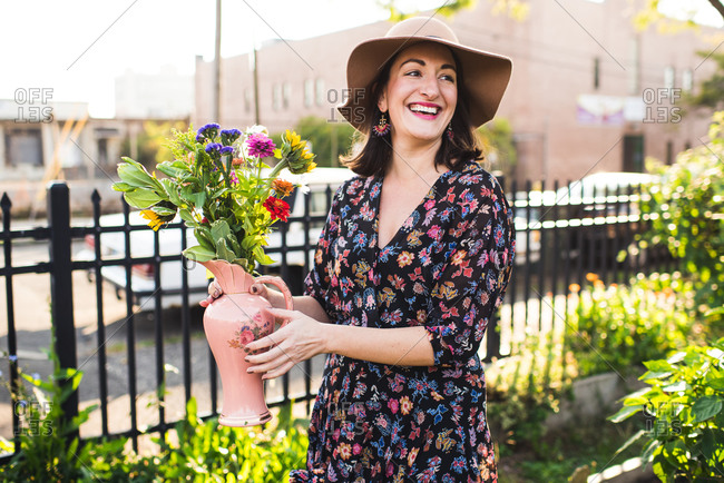 happy woman smiling in urban garden with fresh flowers